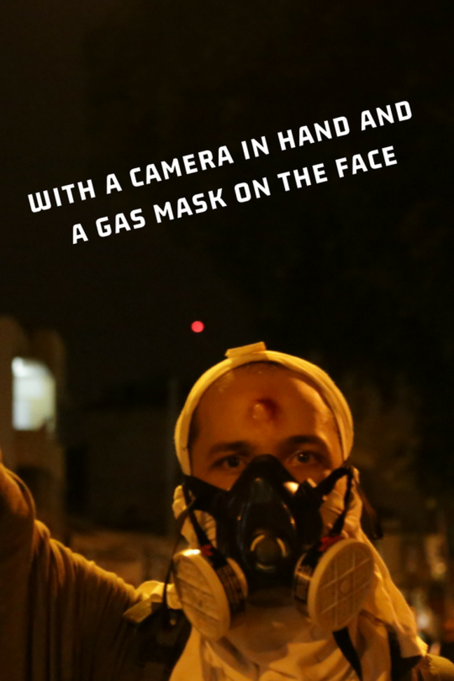 With a camera in hand and a gas mask on the face